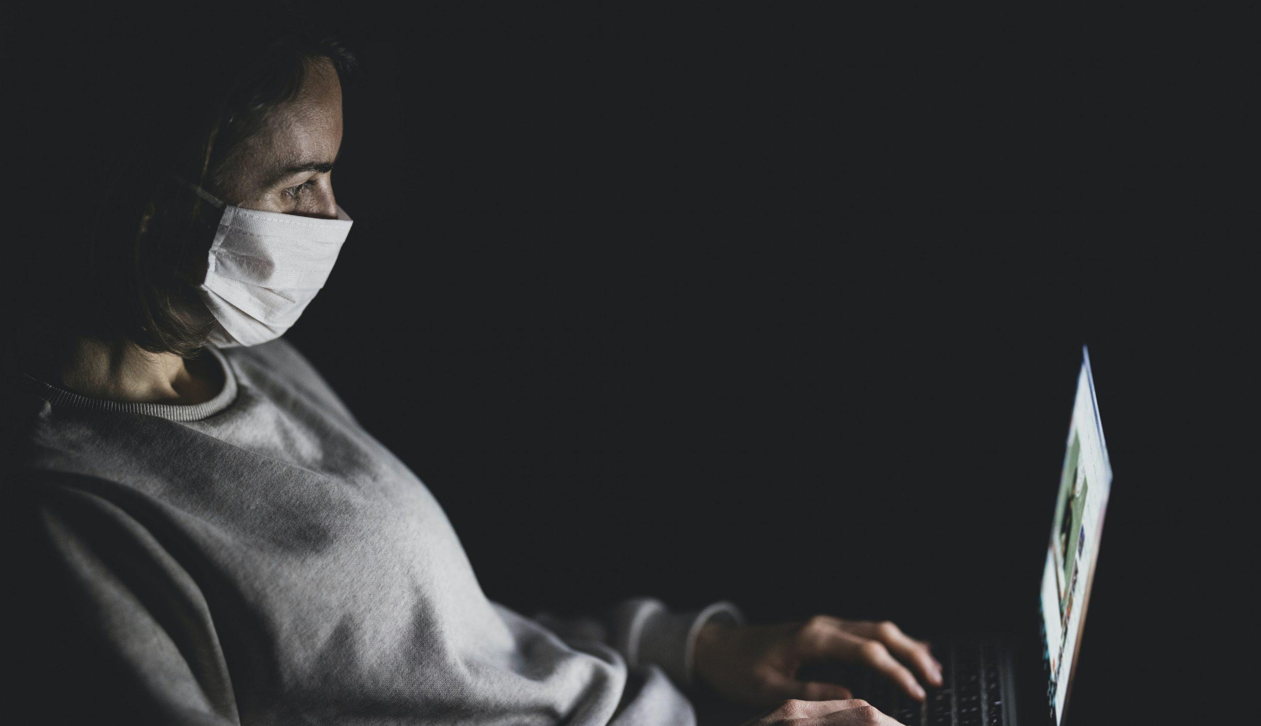 Stock Image – woman mask laptop dark (cropped2)